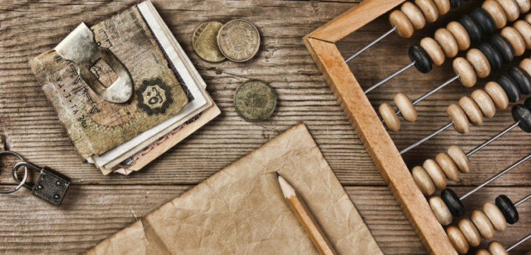 Old notes and coins and abacus on a wooden table