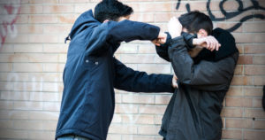 A scene of bullying between two adult teenagers, the guy on the left is about to hit the other guy with his fist, the scene takes place in front of a red bricks wall with graffiti.